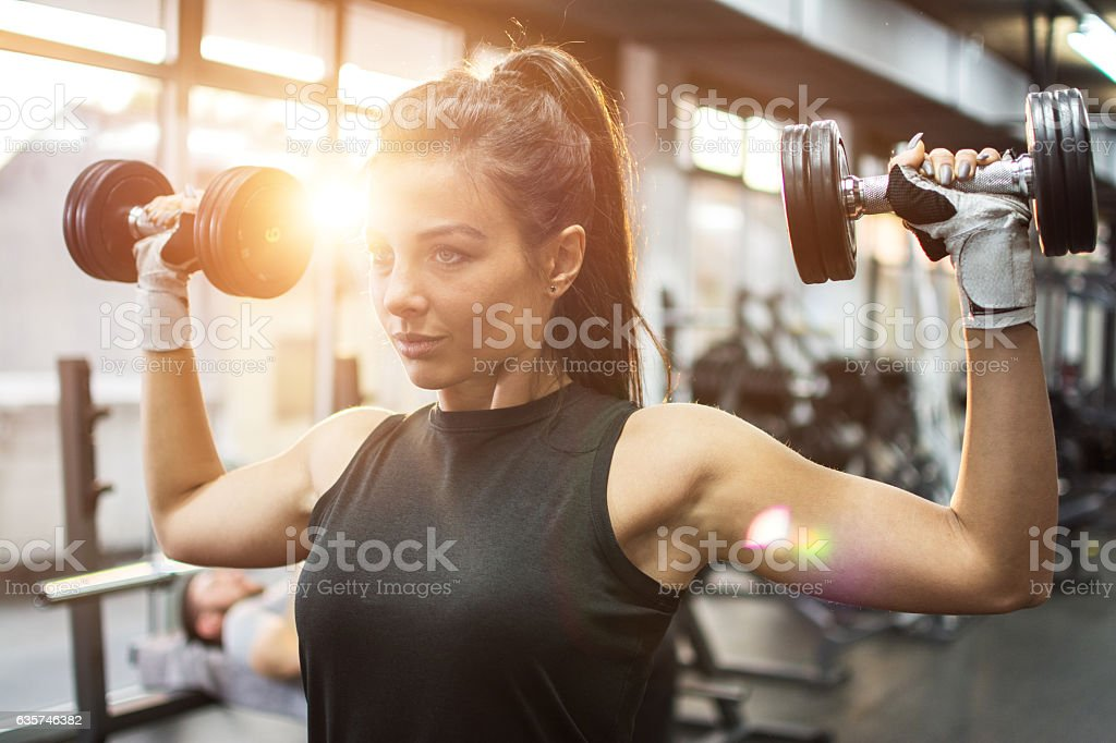 Beautiful young woman working out with dumbbells in gym. - foto de stock