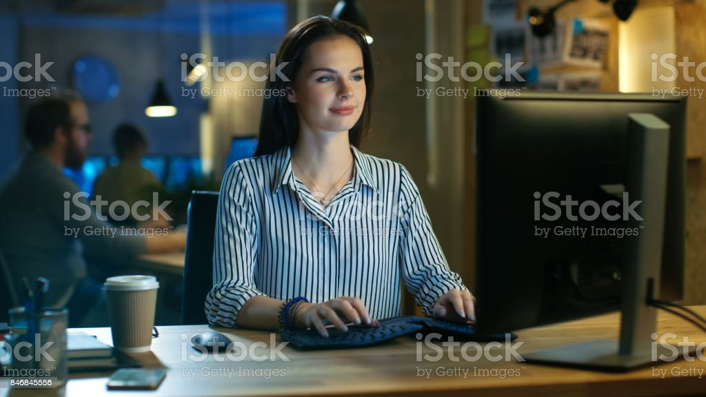 Beautiful Young Woman Works on Personal Computer, She Charmingly Smiles into Camera. She Works in a Modern Office Loft Studio Space. stock photo