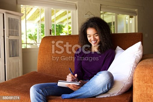 istock Beautiful young woman writing ideas in book 530491274