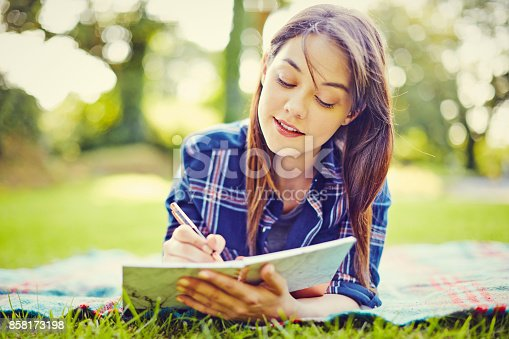 istock Beautiful young woman writing in diary while lying at park 858173198