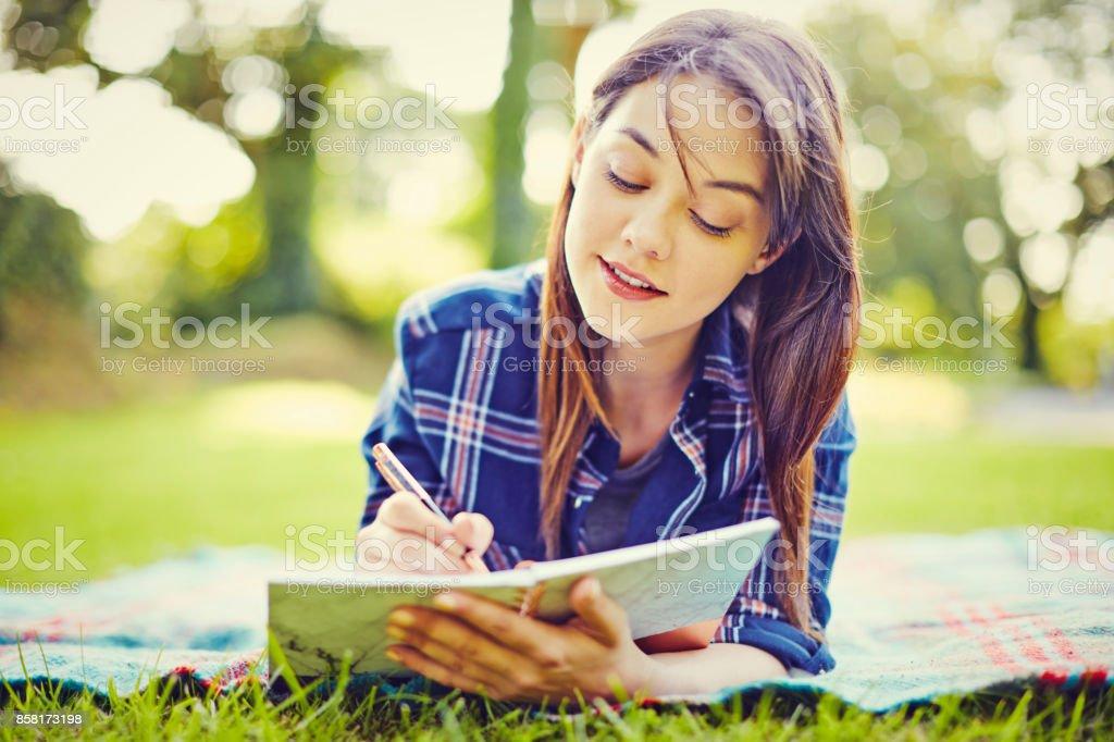 Schöne junge Frau in Tagebuch zu schreiben, beim liegen im park – Foto