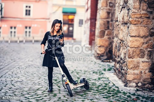 874772840istockphoto Beautiful young woman writing text message while riding electric scooter on urban streets 874772840