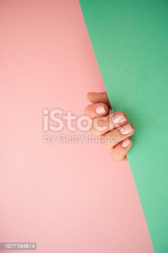 1128559926 istock photo Beautiful young woman's hand on pink and yellow background. 1077194814