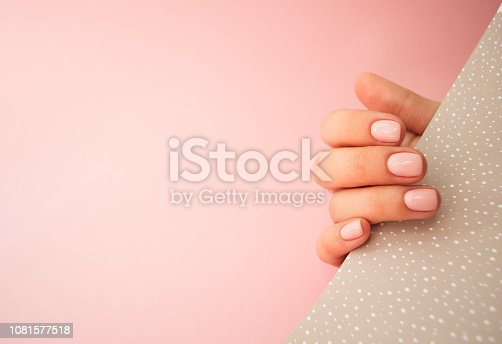 1128559926 istock photo Beautiful young woman's hand on pink and yellow background. 1081577518