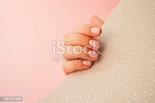 1128559926 istock photo Beautiful young woman's hand on pink and yellow background. 1084251556