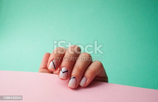 1128559926 istock photo Beautiful young woman's hand on pink and yellow background. 1098433344