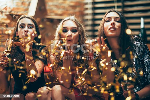 627933752istockphoto Beautiful young women blowing confetti on party 884833538