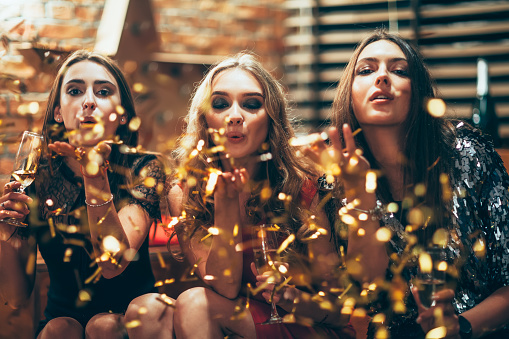 627933752 istock photo Beautiful young women blowing confetti on party 884833538