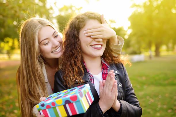 Hermosas mujeres jóvenes da un regalo de cumpleaños a su amigo - foto de stock