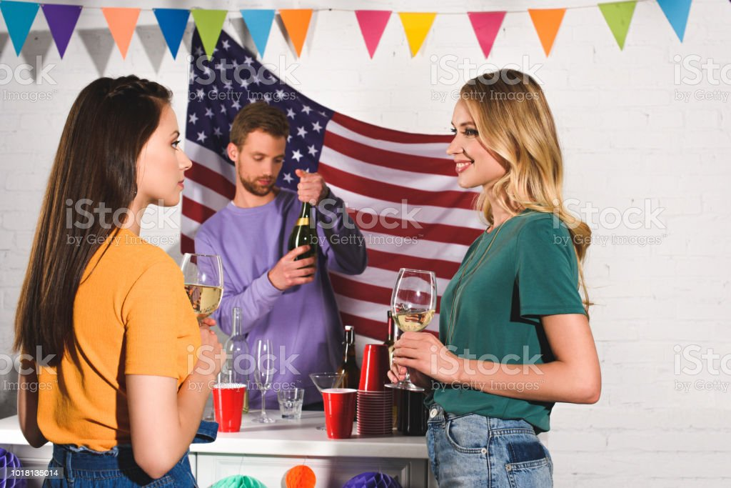 beautiful young women holding glasses of wine and looking at each other while man opening wine bottle behind stock photo