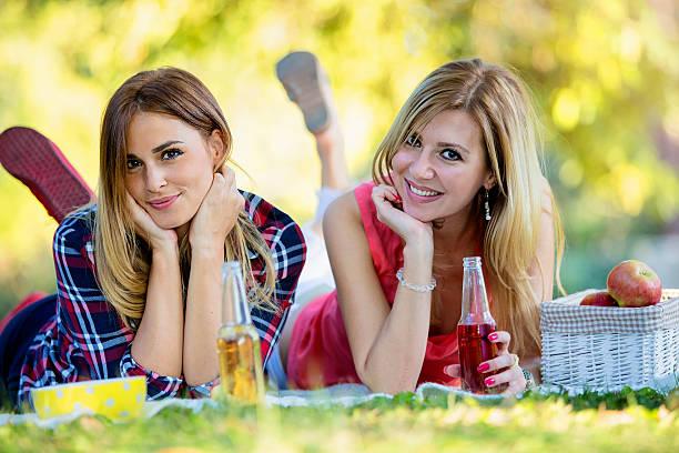 beautiful young women in the park laying on the grass - bier gesund stock-fotos und bilder