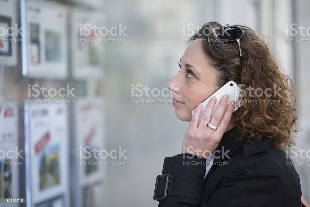 beautiful young women looking at real estate announcement stock photo