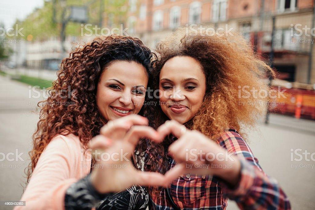 Beautiful young women making heart shape stock photo