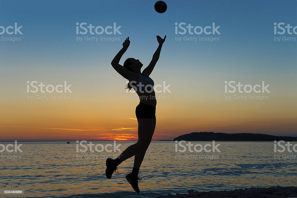Beautiful young women serving the ball against sunset stock photo