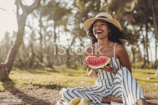 Beautiful young women sitting in the nature and eating watermelon