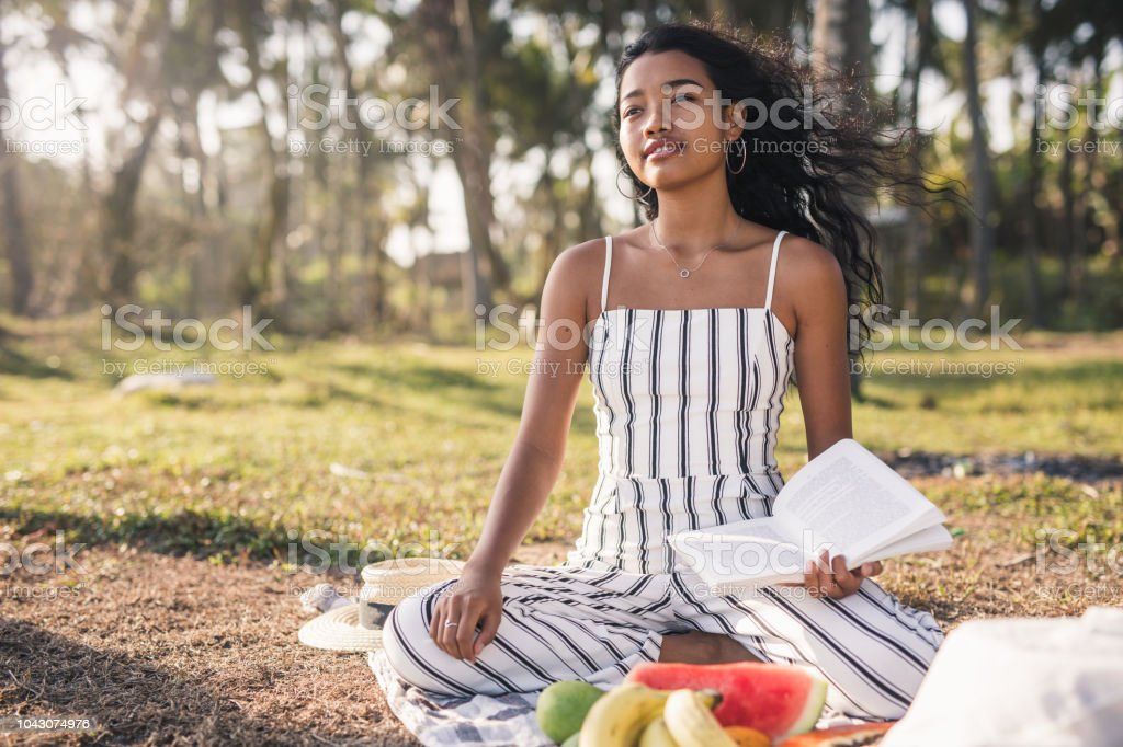 Beautiful young women sitting in the nature and reading book