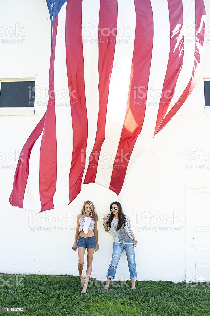 Beautiful Young Women Standing By An American Flag Against Wall royalty-free stock photo