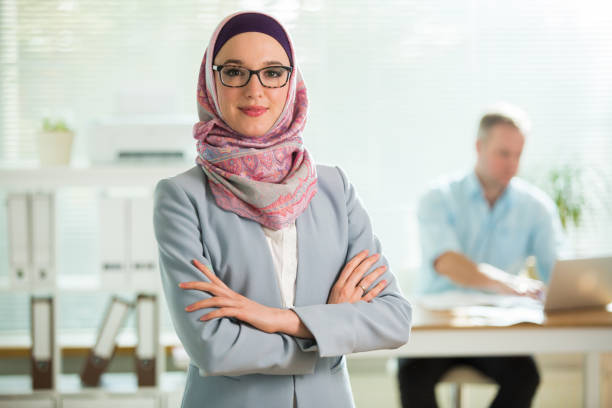 beautiful young working woman in hijab, suit and eyeglasses standing in office - скромная одежда стоковые фото и изображения