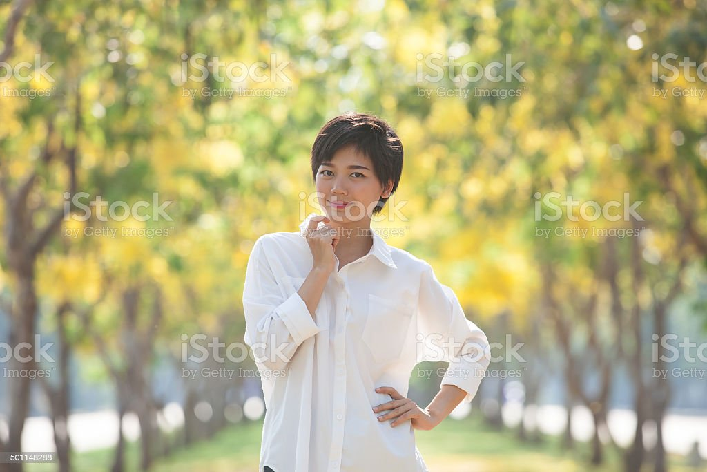 beautiful younger woman standing in yellow blooming flower park stock photo