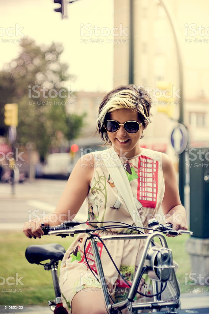 beautiful younggirl in a white skirt and sunglasses riding bicycle stock photo