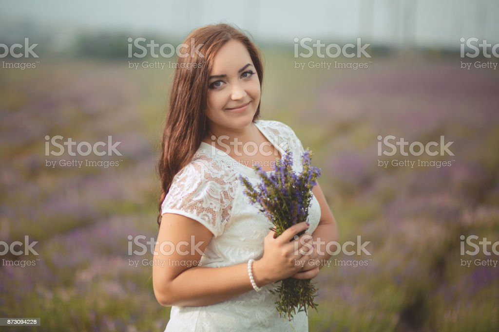 Beautifull brunette buxom nubile lady woman with deep blue eyes posing on field of spring lavender wearing cute cozy white hand made dress and holding basket with summer flowers stock photo