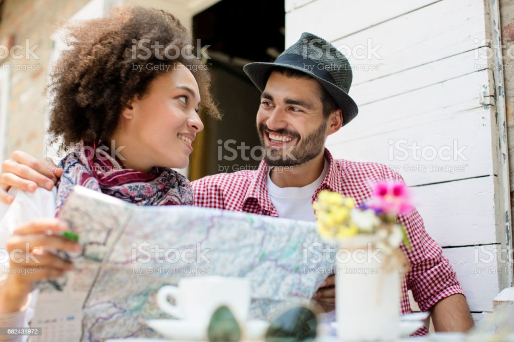 Beautifull couple smiling while looking map royalty-free stock photo