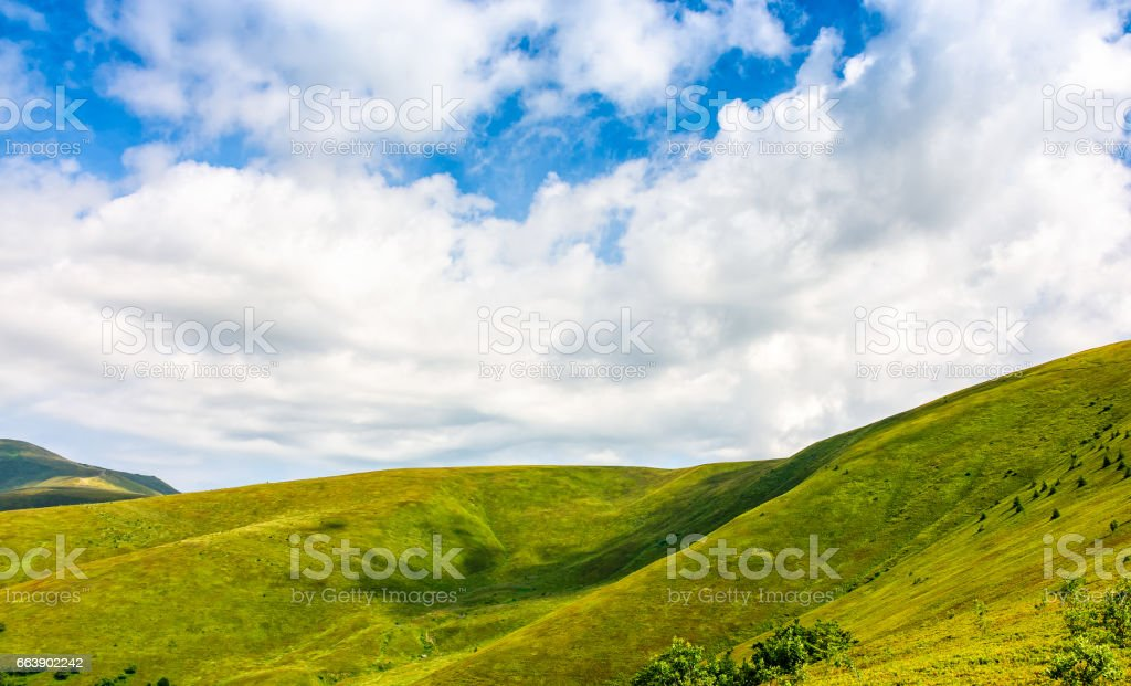 deep blue sky with some clouds over the green and grassy hills of...