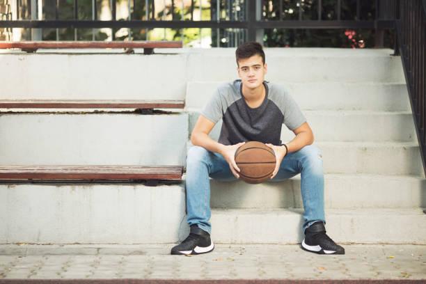 Beautifull teenage boy with basketball ball stock photo