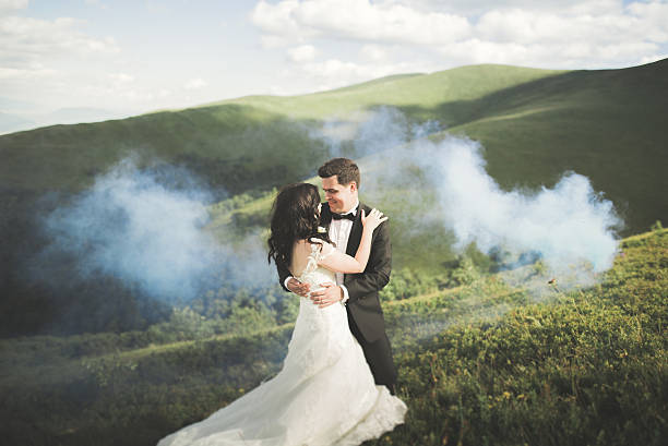 Beautifull wedding couple kissing and embracing near mountain with perfect stock photo