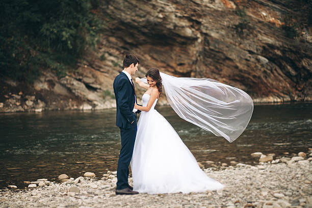 Beautifull wedding couple kissing and embracing near the shore of stock photo