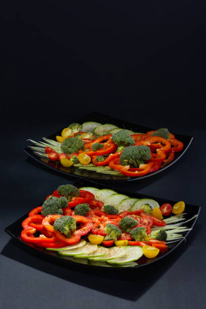 Cтоковое фото Beautifully and appetizingly cut fresh vegetables and cabbage of broccoli on two black ceramic plates
