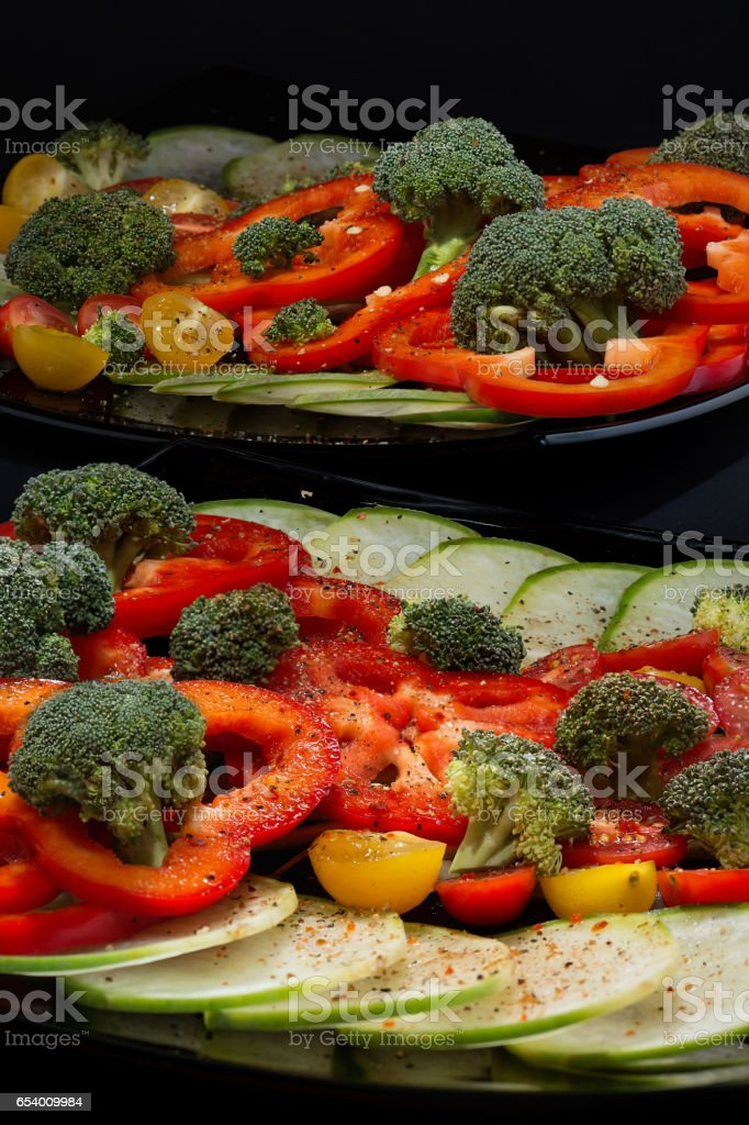 Beautifully and appetizingly cut fresh vegetables and cabbage of broccoli on two black ceramic plates close up стоковое фото