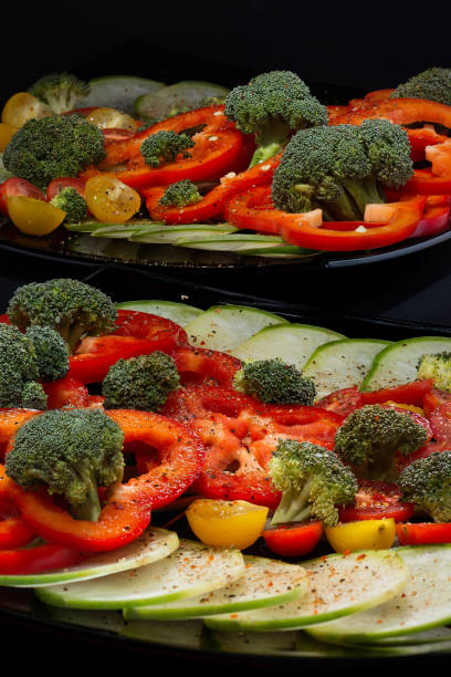 Cтоковое фото Beautifully and appetizingly cut fresh vegetables and cabbage of broccoli on two black ceramic plates close up