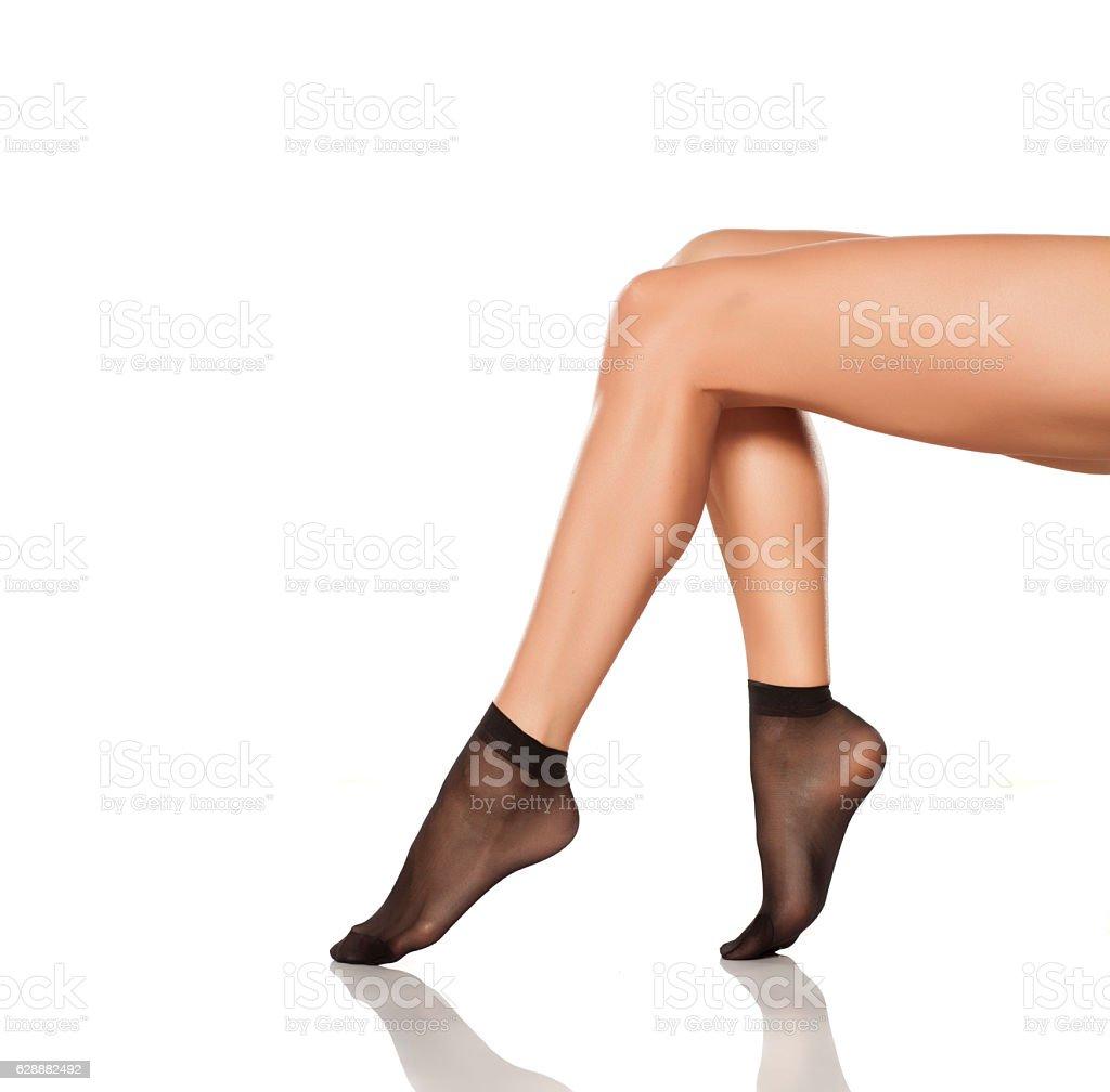 beautifully cared feminine legs in a black short nylon socks stock photo