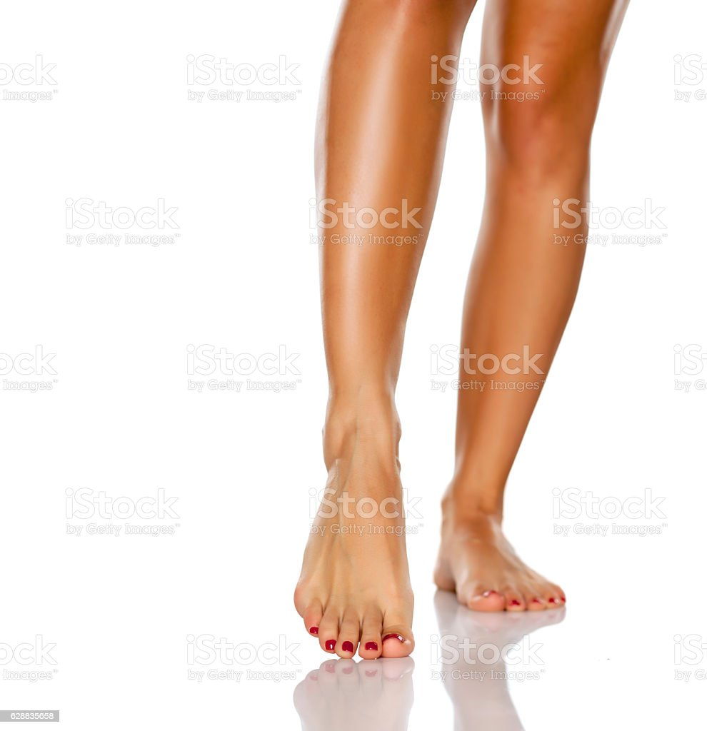 beautifully cared women's legs and feet on white background stock photo