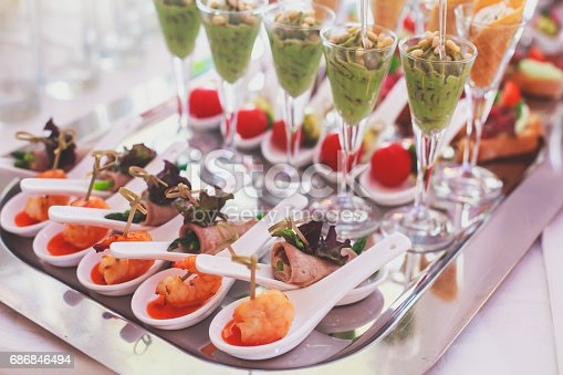 istock Beautifully decorated catering banquet table with different food snacks and appetizers on corporate christmas birthday party event or wedding celebration 686846494