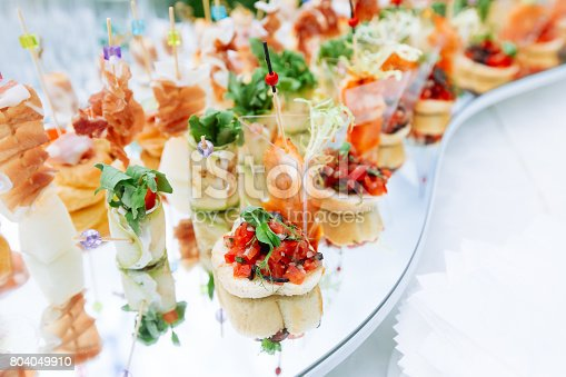 Beautifully decorated catering banquet mirror  table with different food snacks and appetizers