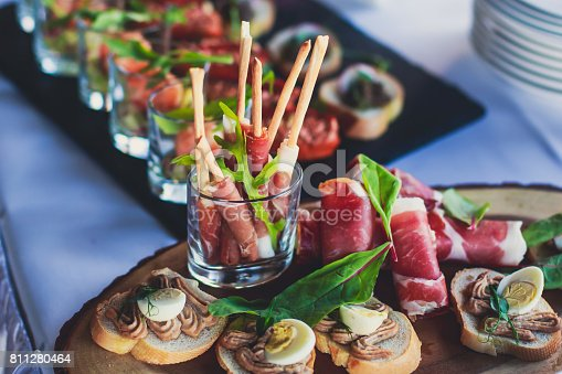 istock Beautifully decorated catering banquet table with different food snacks and appetizers on corporate christmas birthday party event or wedding celebration 811280464