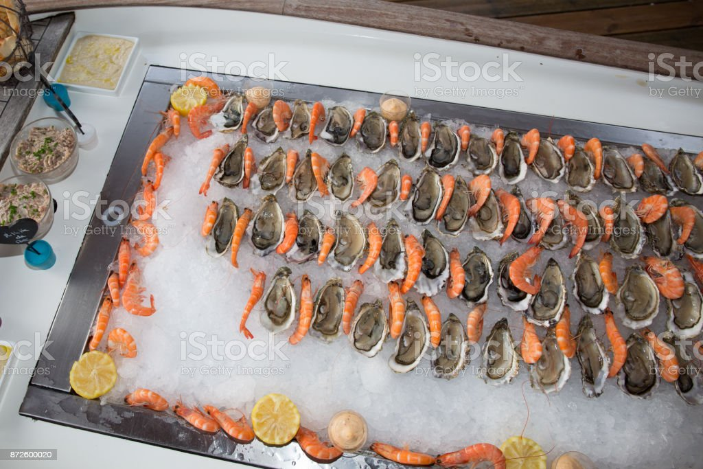 Beautifully decorated catering banquet table with oysters, mussels and seafood with ice and lemon on corporate christmas birthday party event or wedding celebration stock photo