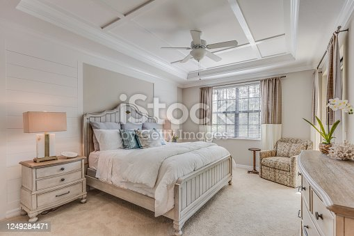 Ceiling fan and coffered ceiling are examples of decorative additions to this bedroom