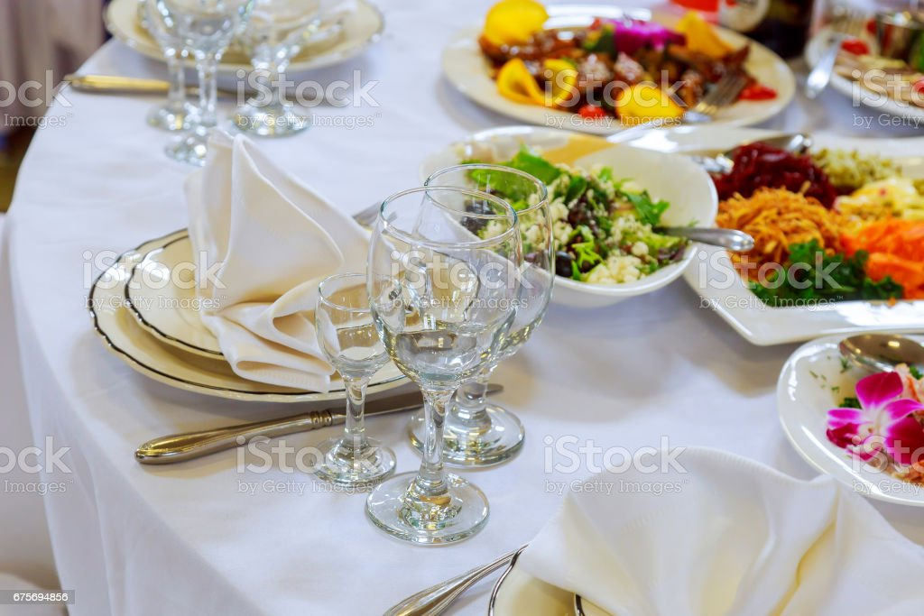 Beautifully decorated table set with flowers, candles, plates and serviettes for wedding or another event in the restaurant royalty-free stock photo