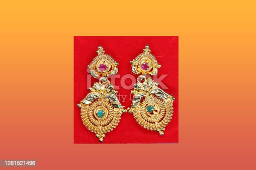 Beautifully designed earrings and a green and red colored stonework view, gold jewels