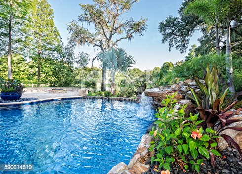 A beautiful landscaped swimming pool at an estate home overlooking a lake in Florida.