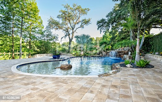 A beautiful landscaped swimming pool with waterfall at an estate home overlooking a lake in Florida.