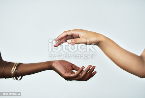 Cropped studio shot of two women touching hands against a gray background