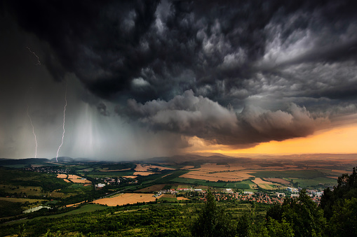 A severe thunderstorm shelf cloud races across the country side on a summer afternoon