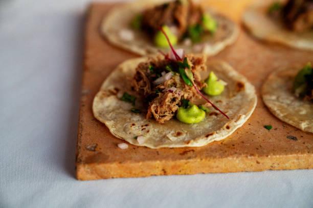 tacos de ternera rallado bellamente estilo en tortillas de maíz con puntos de guacamole - comida mexicana fotografías e imágenes de stock