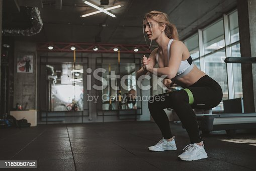 istock Beautifulyoung athletic woman working out at the gym 1183050752