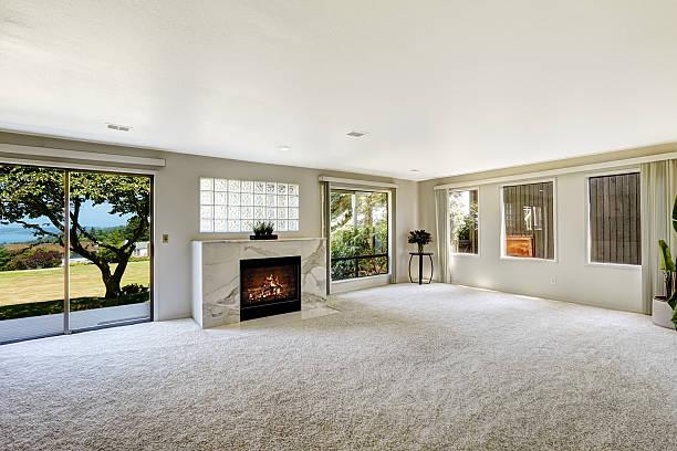beautitful living room with fireplace and walkout deck - tapijt stockfoto's en -beelden