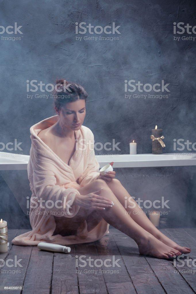 Beauty 29 years woman applying body lotion on her legs. Sitting on the hardwood floor in bathrobe. stock photo